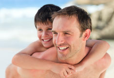Father having son a piggyback on the beach Royalty Free Stock Photos