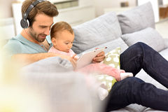 Father with headphones holding his baby girl playing on tablet Royalty Free Stock Photo