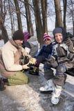Father help children to wear skates Stock Photos