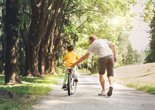 Father help his son ride a bicycle Royalty Free Stock Images