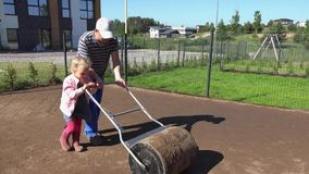 Father and helper girl level ground with roller in townhouse yard. lawn seeding. Father and his helper girl leveling soil ground with huge roller tool in stock video