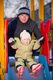 Father helping baby to slide down on playground. Father helping baby to slide down Stock Images
