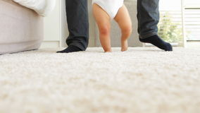 Father helping baby to walk across rug