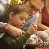 Father helping boy with cake. Caucasian mid adult father helping son with birthday cake royalty free stock image