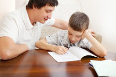 Father helping boy do homework Stock Images