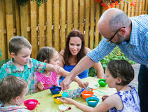 Father Helping Children Dyeing Their Easter Eggs. A family picture of children having fun painting and decorating eggs outside.  A father helps his children dye Royalty Free Stock Image