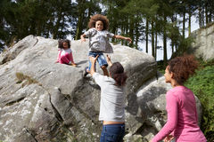 Father Helping Children To Jump Off Rocks Royalty Free Stock Images