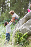 Father Helping Children To Jump Off Rocks Royalty Free Stock Image