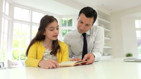 Father Helping Daughter With Homework In Kitchen stock video footage