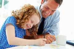 Father Helping Daughter With Homework In Kitchen Stock Photos