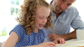 Father Helping Daughter With Homework In Kitchen stock footage