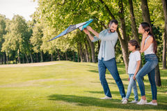 Father helping daughter launching kite while spending time together Royalty Free Stock Image