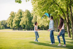 Father helping daughter launching kite while spending time together royalty free stock photography