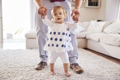 Father helping daughter learn to walk in the sitting room stock photo