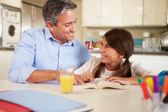 Father Helping Daughter With Reading Homework At Table. Smiling At Each Other Stock Photos