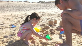 Father Helping Daughter To Build Sandcastle On Beach stock video footage