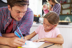 Father Helping Daughter To Draw Picture At Kitchen Table Royalty Free Stock Images