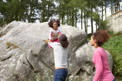 Father Helping Daughter To Jump Off Rocks Stock Photo