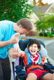 Father helping disabled son adjust arm guards orthotics. Caucasian father helping disabled ten year old son in wheelchair adjust orthotic arm guards outdoors Royalty Free Stock Photography