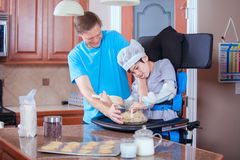 Father helping disabled son bake cookies in kitchen Stock Photography