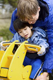 Father helping disabled son play. On playground equipment royalty free stock images