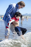Father helping disabled son walk in the ocean waves on beach Stock Image