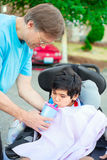Father helping disabled son in wheelchair drink from straw cup Royalty Free Stock Image