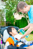 Father helping disabled son in wheelchair drink from straw cup Royalty Free Stock Photos