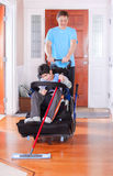 Father helping disabled son in wheelchair mop the floor Royalty Free Stock Photo