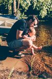 Father helping his baby to test the water. On the shore of a finnish lake, the boy is splashing the water with his feet royalty free stock image
