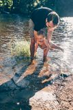 Father helping his baby to test the water. On the shore of a finnish lake, the boy is safe in his father arms and laughs stock photo