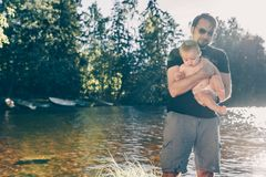 Father helping his baby to test the water. On the shore of a finnish lake, the boy is safe in his father arms royalty free stock photos
