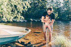 Father helping his baby to test the water. On the shore of a finnish lake, the boy is safe in his father arms Royalty Free Stock Image