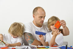 Father helping his children with art projects. There are two young boys and a man, all dressed in white shirts Royalty Free Stock Photos