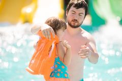 Father helping his cute toddler daughter with her life jacket in outdoors swimming pool in water park aquapark. Father helping his cute toddler daughter with her royalty free stock photos