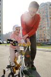 Father helping his daughter riding bicycle Royalty Free Stock Photos