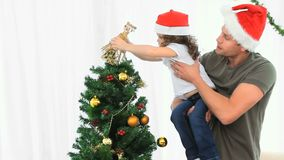 Father helping his daughter to decorate the Christmas tree stock video