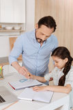 Father helping his daughter to inscribe a circle Royalty Free Stock Photo