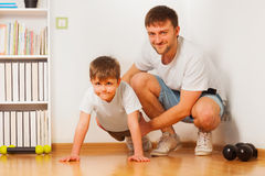 Father helping his kid son doing press-ups at home Royalty Free Stock Photos