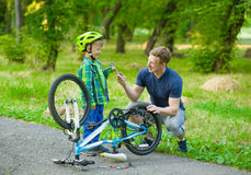 Father helping his son bicycle repair Stock Image