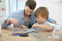 Father helping his son building an aeroplane toy. Father and son assembling airplane mock-up Royalty Free Stock Photo