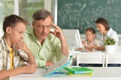 Father helping his son doing homework in classroom royalty free stock photography