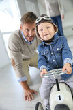 Father helping his son driving car toy Royalty Free Stock Images