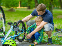 Father helping his son fix bicycle Stock Images