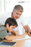 Father helping his son with his homework. In a house Stock Photo
