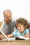 Father helping his son with his homework. The young boy is writing in a copy book. There's an abacus on the table stock image