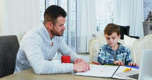Father helping his son with homework 4k. Father helping his son with homework at home 4k stock footage