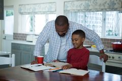 Father helping his son with homework in kitchen. At home Stock Images