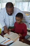 Father helping his son with homework in kitchen. At home Stock Photography