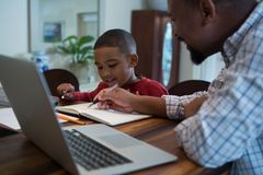 Father helping his son with homework in living room. At home Stock Images